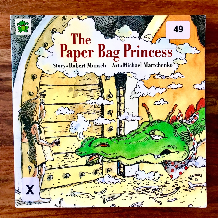 The image is a photograph of the cover of the book The Paper Bag Princess by Robert Munsch. The cover features an illustration of the paper bag princess facing a dragon.