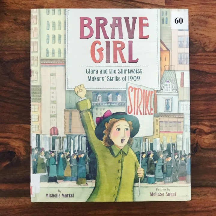 "A photo of a book cover. The cover says ""Brave Girl: Clara and the Shirtwaist Makers' Strike of 1909"" and features a drawing of a woman dressed in a green coat with one fist in the air and holding a picket sign that says ""strike."" In the background are women marching through the city and holding picket signs."