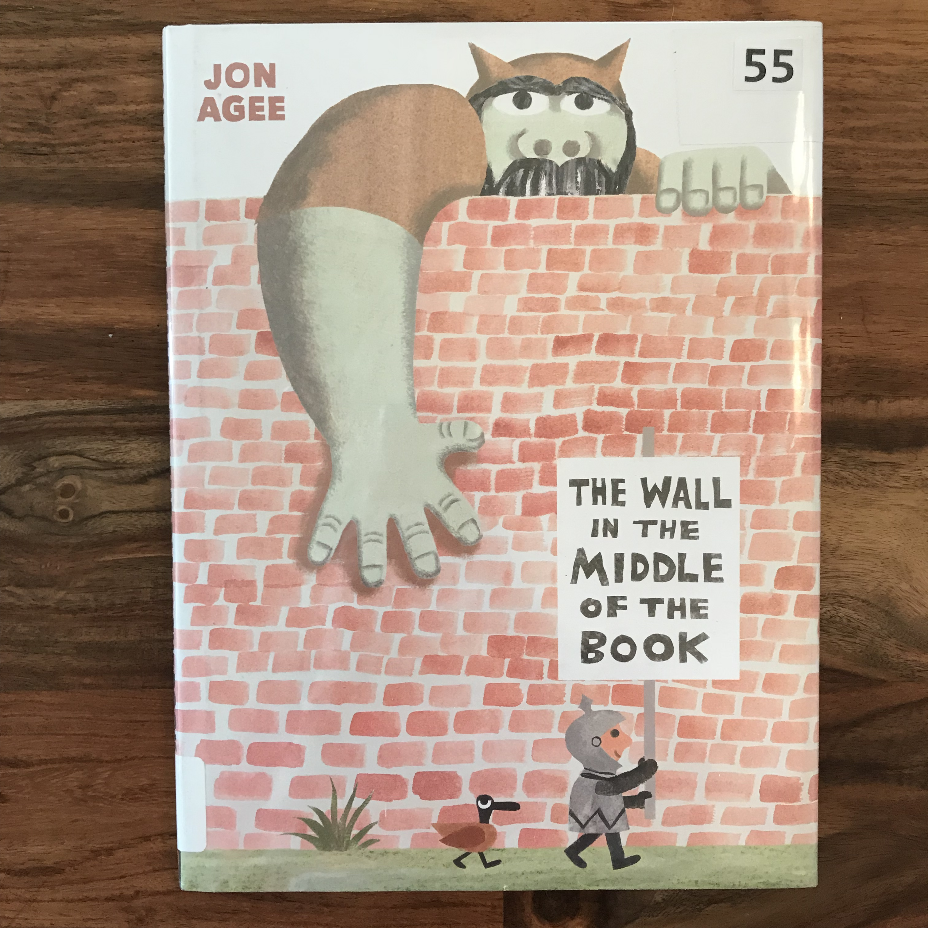 "The cover of ""The Wall in the Middle of the Book"" shows a knight standing on one side of a brick wall holding a sign with the title of the book. Behind the wall is an ogre who is reaching a large hand over the top of the wall."