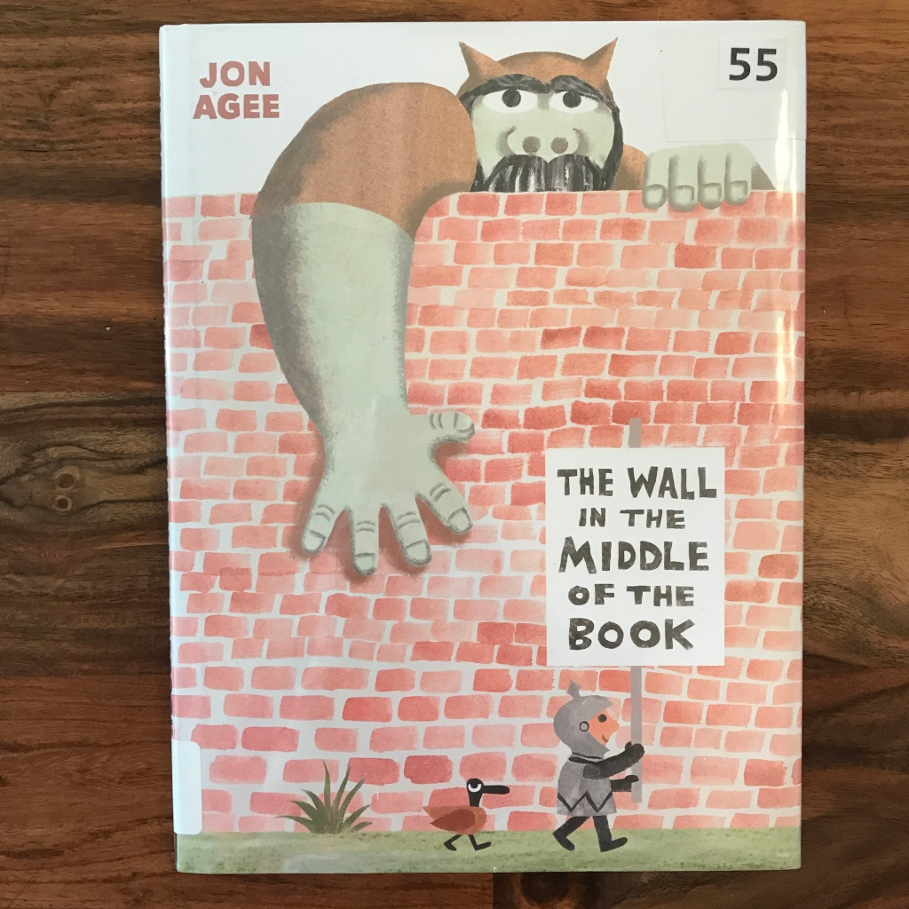 """The cover of """"The Wall in the Middle of the Book"""" shows a knight standing on one side of a brick wall holding a sign with the title of the book. Behind the wall is an ogre who is reaching a large hand over the top of the wall."""