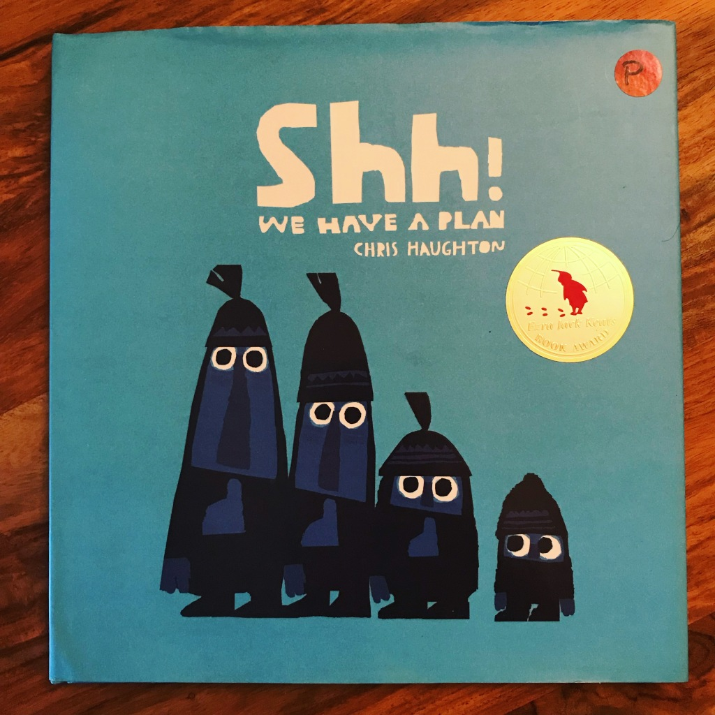 "A blue book cover with the title ""Shh! We Have a Plan!"" written across the top in white letters. There are 4 character silhouettes with white eyes, the fourth is the smallest and is looking sideways at the other three. The book has a gold Ezra Jack Keats award sticker."