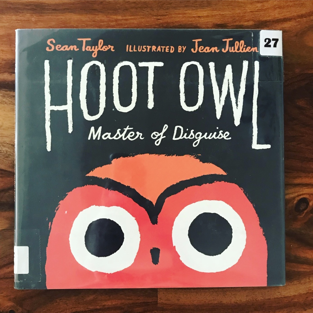 """The image is a photograph of a book cover. The book says """"Hoot Owl Master of Disguise"""" in white letters on a black background. Below the title is a large red and orange cartoon owl's face."""